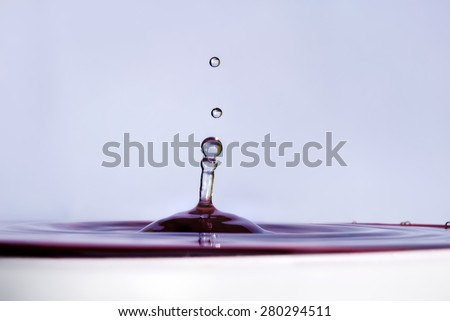 Water drop falling into water and making droplet splash. Shallow depth of field. Selective focus. Lilac shade water. - stock photo