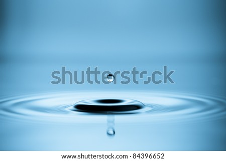 Water drop falling into water making a perfect droplet splash