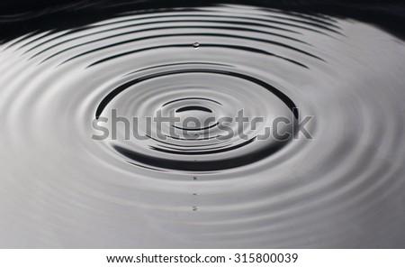 Water drop falling into water making droplet splash - stock photo