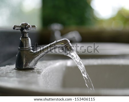 Water drop from faucet - stock photo