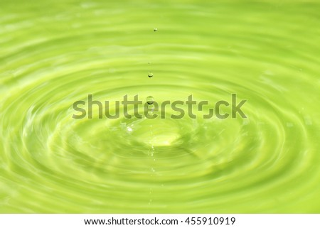 Water drop impact on water surface green background - stock photo