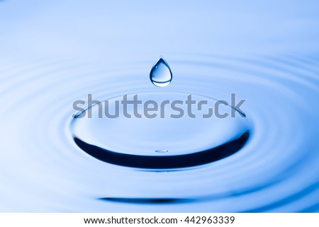 Water drop  in to blue water - stock photo