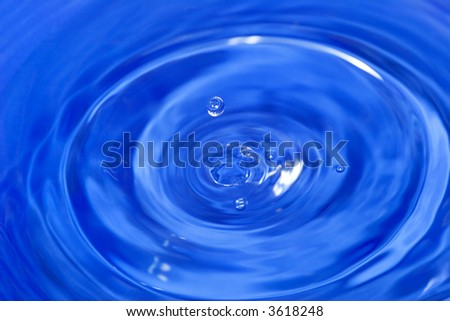 water drop is falling down and impact with water surface - stock photo