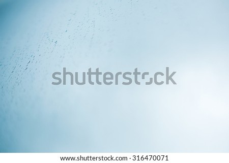 water drop on blue glass background - stock photo