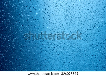 water drop on blue metal surface as background - stock photo