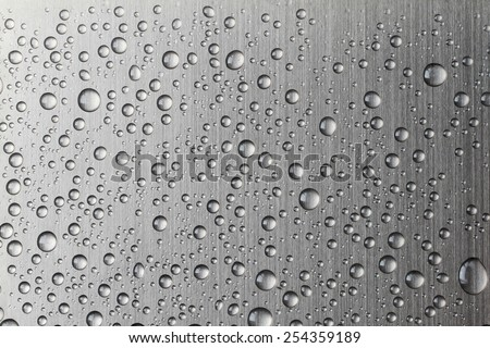 Water drop on Brushed metal texture ; abstract industrial background  - stock photo