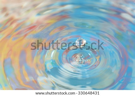 Water drop on colorful backround - stock photo
