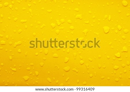 water drop on yellow metal - stock photo