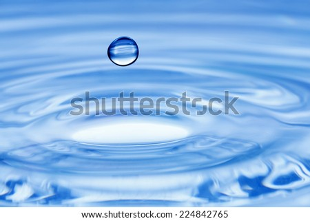 water drop over rippled water surface - stock photo