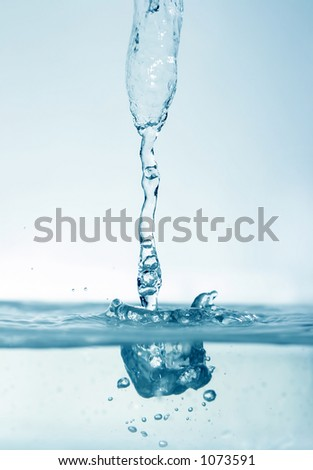 water droplets captured while descending on to the still water surface - stock photo