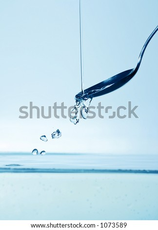 water droplets captured while descending on to the still water surface with spoon - stock photo