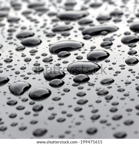 Water droplets closeup on polished surface - stock photo
