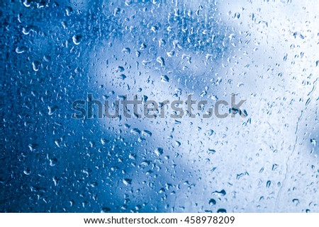 Water droplets from rain on glass, blue background