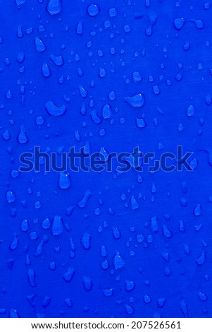 Water droplets on a blue metal background. - stock photo