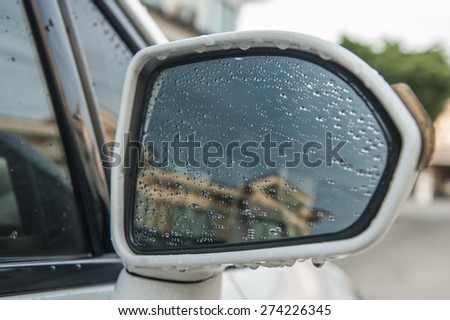 Water droplets on a car side mirror.