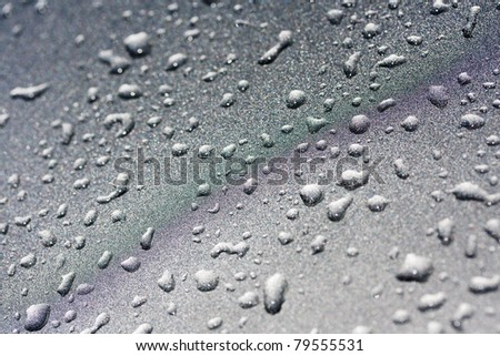 Water droplets on a silver metallic background