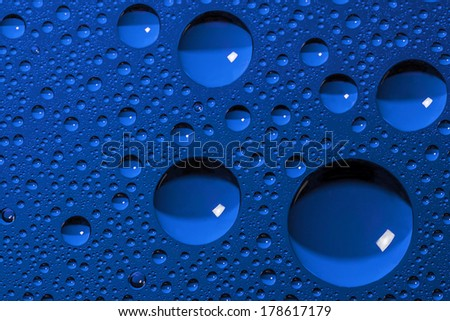 Water droplets on glass panel blue - stock photo
