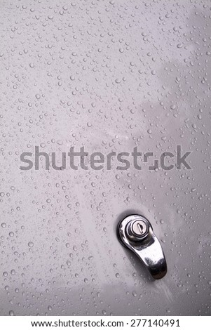 Water droplets on metallic gray trunk lid - stock photo