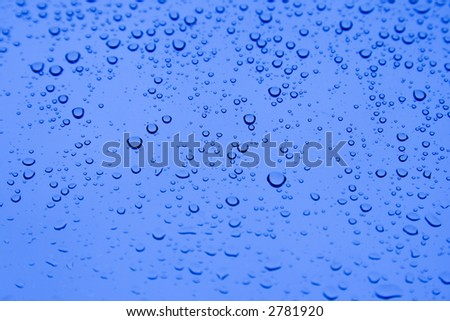 Water droplets on the glass window with blue sky background