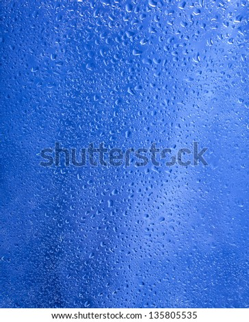Water droplets on the glass with a blue background. Drops of water. - stock photo