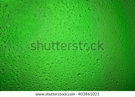 Water droplets on the glass with a green illumination - stock photo