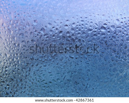 water drops and frost on window glass - stock photo