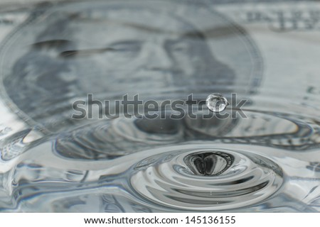 water drops and ripples with a one hundred dollar bill as a background and reflection - stock photo