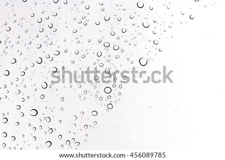 Water drops background. Water drops on glass window over blue sky. - stock photo