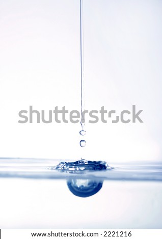 water drops caught falling to calm surface - stock photo