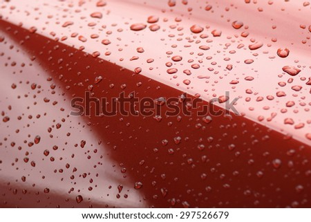 Water drops collect on top of metal red car surface - stock photo
