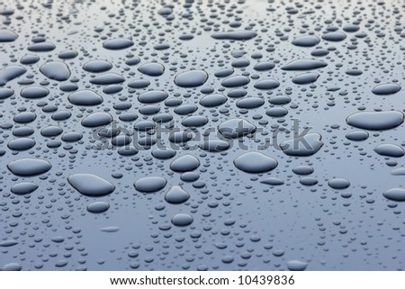 Water drops in blue reflected metallic surface