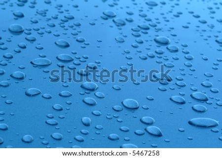 Water drops in blue textured metallic surface - stock photo