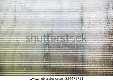 Water drops of condensation on a transparent plastic polycarbonate surface  - stock photo