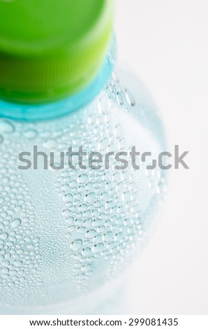 Water drops on a blue plastic water bottle. - stock photo