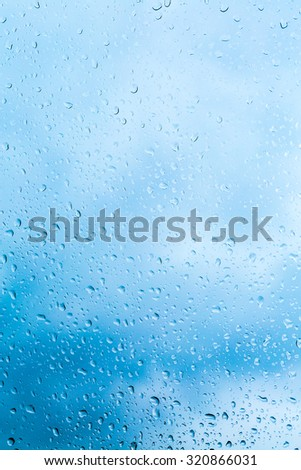 Water drops on a window glass after the rain. The sky with clouds on background. - stock photo
