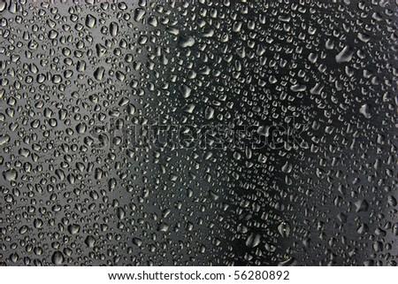 water drops on black metallic surface - stock photo
