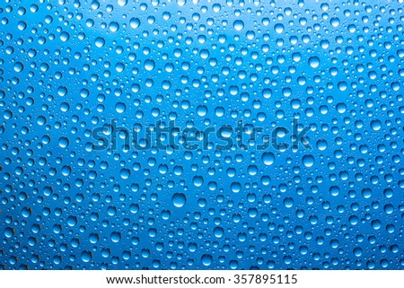 Water drops on blue glass surface texture.