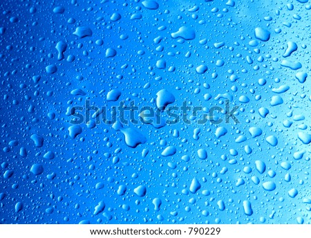 Water drops on blue surface (a bit grainy because of metallic car paint) - stock photo
