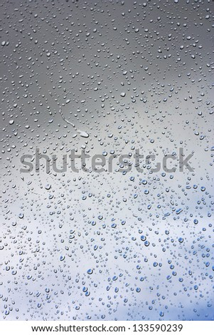 Water drops on glass against the sky