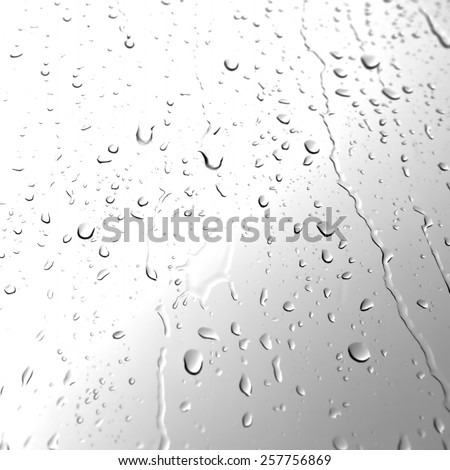 Water drops on glass in monochrome - stock photo