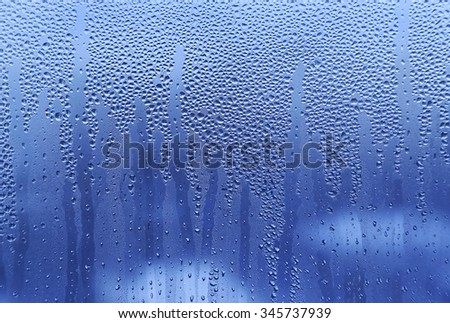 Water drops on glass naural bright blue background