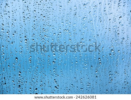 Water drops on glass texture or background. Blue tint. - stock photo