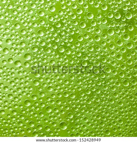 Water drops on green glass in the background - stock photo
