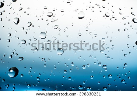 Water drops on mirror blue and white abstract background