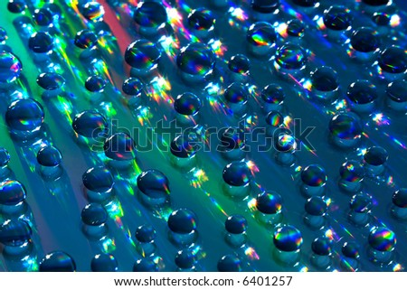 Water drops on reflective surface. Hard lighting produces rainbow-like effect on the background and the drops themselves. Light bounces everywhere and is refracted as it passes through the drops. - stock photo