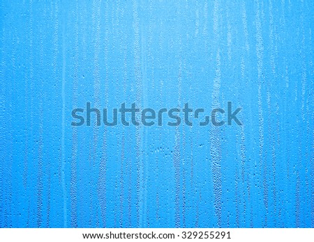 Water drops on steamed up window overlaid with blue color - stock photo