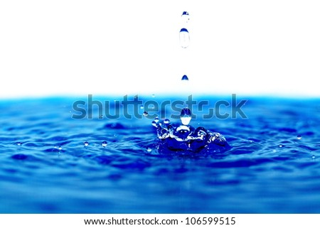 Water drops on the clear water. - stock photo