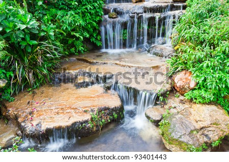 Water fall over rocks - stock photo