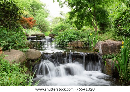 Water fall over rocks in forest - stock photo