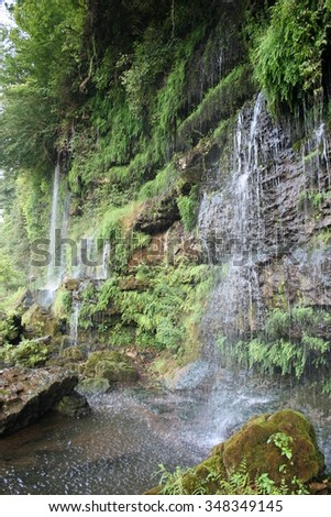 Water falling down a mossy stone cliff